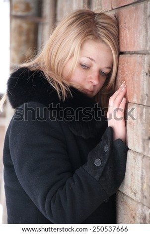 Young woman in winter is standing against the wall of the house