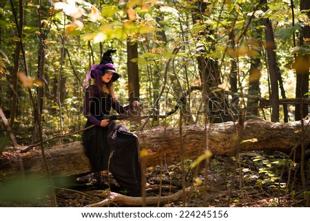 young woman in witch's hat sitting on tree and holding broom