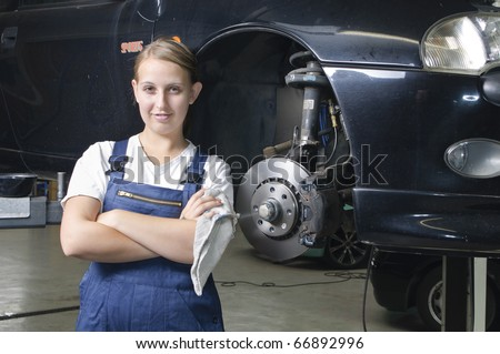 Young woman in work clothes, Apprentice is next to a car and is proud and happy in a garage - stock photo