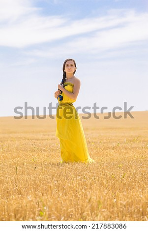 Young  woman in yellow dress in wheat field
