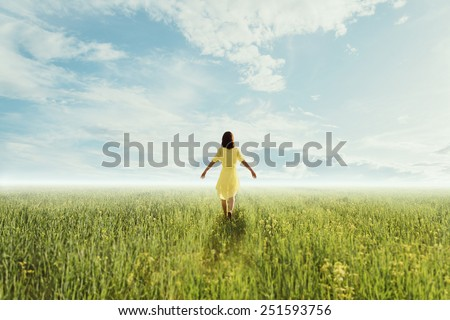Young woman in yellow dress walking on summer meadow at sunny day, rear view. Image with sunlight effect. Concept of happiness and carefree - stock photo