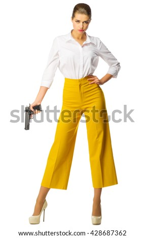 Young woman in yellow pants with gun isolated - stock photo
