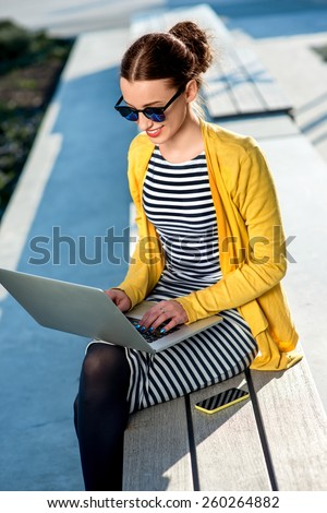Young woman in yellow sweater working with laptop and phone on the bench in the city - stock photo