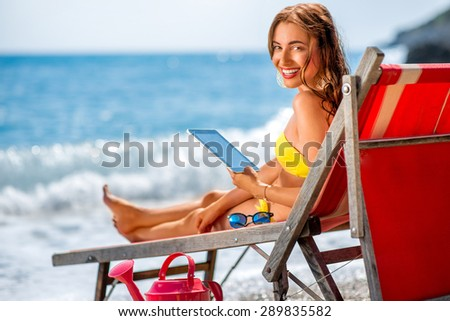 Young woman in yellow swimsuit using digital tablet lying on the red sunbed on the beach - stock photo