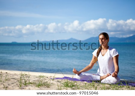 Young woman in yoga pose on the beach