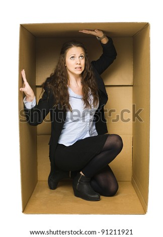 Young Woman inside of a tight Cardboard Box - stock photo