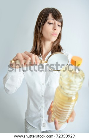 Young woman inspecting a bottle of oil with a magnifying glass - stock photo