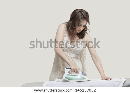 Young woman ironing shirt against gray background - stock photo