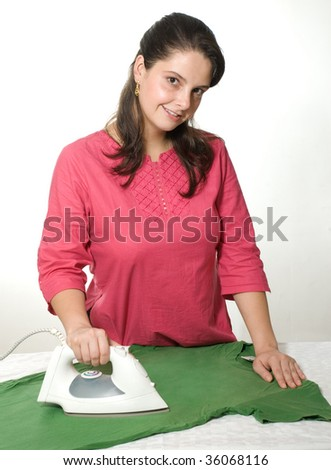 Young woman ironing shirt happily