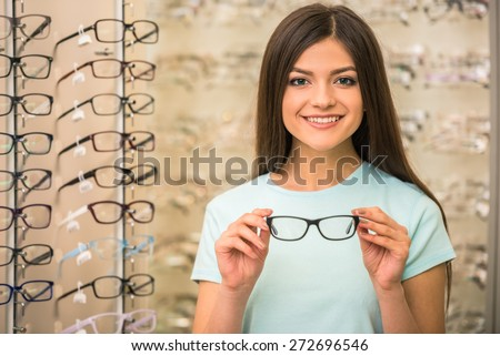 Young woman is choosing a glasses in optician store. - stock photo