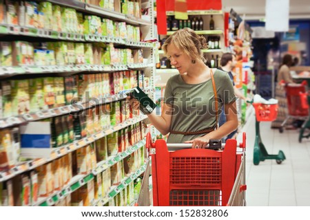 Young woman is choosing food for diet in supermarket - stock photo
