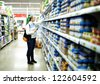 Young woman is choosing food for her child at the food store. Wide shot, shallow dof. - stock photo
