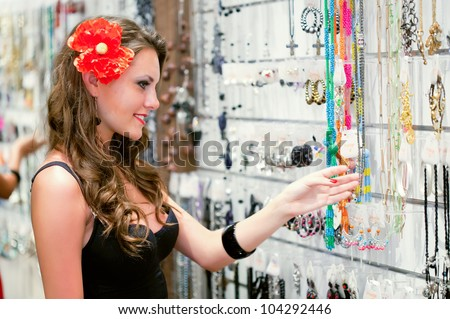 Young woman is choosing jewelry in the shop - stock photo