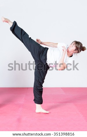 young woman is doing a kick in a capoeira session indoor - focus on the face - stock photo