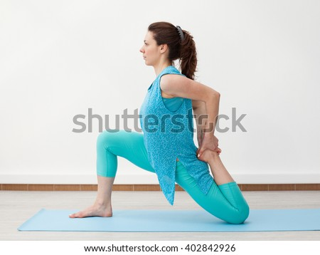 Young woman is doing stretching on the mat, touching the foot, profile view, white background - stock photo