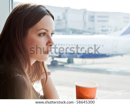 Young woman is drinking coffee in airport - stock photo