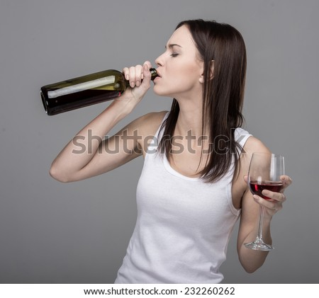Young woman is drinking wine from bottle. - stock photo