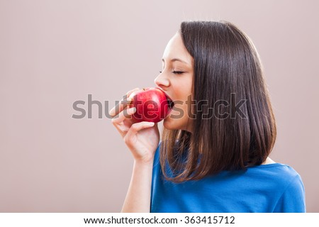 Young woman is eating an apple. Healthy nutrition. - stock photo