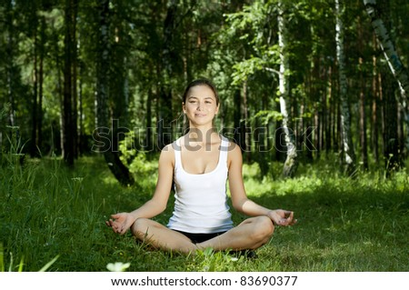 young woman is engaged in yoga, in summer forest on a green grass