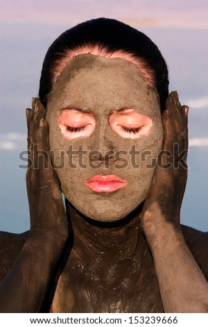 Young woman is enjoying the natural mineral mud sourced from the Dead Sea,  Israel. - stock photo