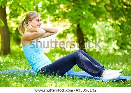 Young woman is exercising in park.