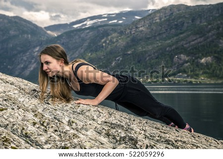Young woman is exercising on the fjord, Norway