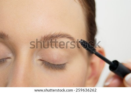 Young woman is getting her makeup. Professional makeup artist at work.