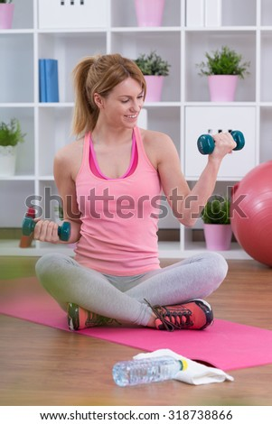Young woman is happy during training with dumbballs