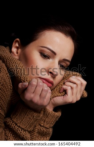 Young woman is having depression. Isolated on black.