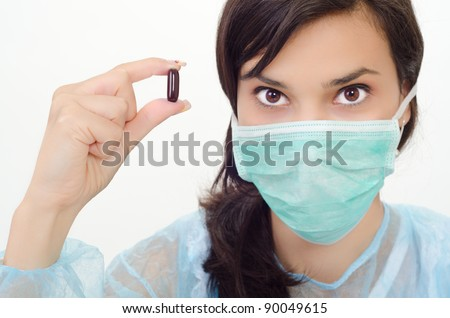 Young woman is holding a brown pill - stock photo