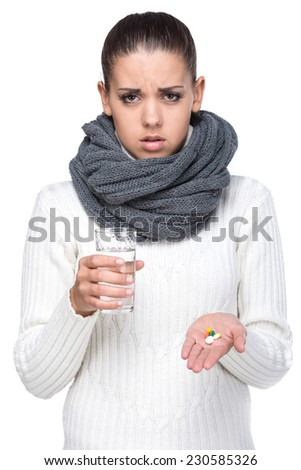 Young woman is holding a glass of water and tablets in hands. On the white background. - stock photo
