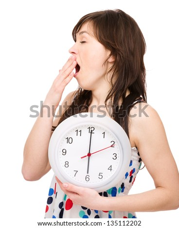 Young woman is holding big clock while yawning, isolated over white - stock photo
