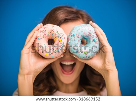 Young woman is  holding donuts against her eyes and smiling while standing against blue background. - stock photo