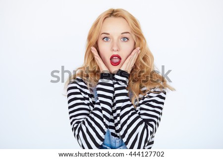 Young woman is holding her face in astonishment isolated over white. Closeup portrait of teenage blond hair girl face with red lips shocked and surprised - stock photo