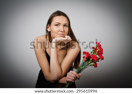Young woman is holding pink flowers. Young woman is doing something - stock photo