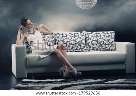 Young woman is lying on a couch .Fashion photo.  - stock photo