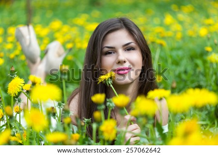 Young woman is lying on field with dandelions - stock photo