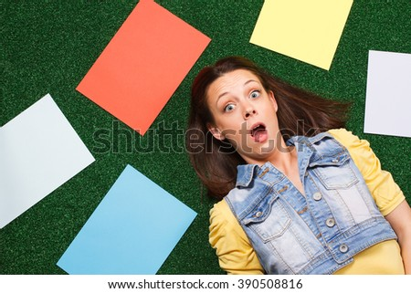 Young woman is lying on the grass surrounded with empty papers and she is in panic because of something.Woman in panic surrounded with empty papers - stock photo