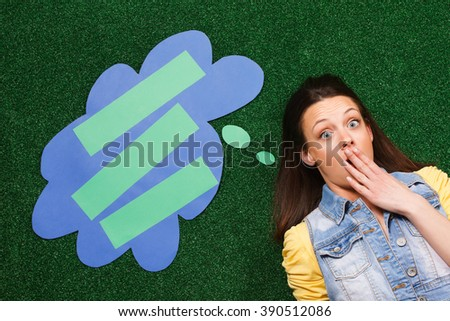 Young woman is lying on the grass with a thought bubble beside her head and she is shocked because of  something.Shocked woman with a a thought bubble - stock photo