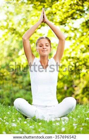 Young woman is meditating in park. - stock photo