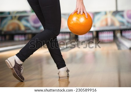 Young woman is playing bowling, preparing to throw ball. - stock photo