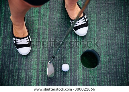 Young woman is playing mini golf. Selective focus - stock photo