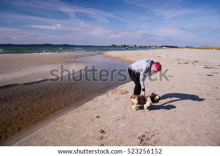 Young woman is playing with dog near North sea on Sola beach close to Sola airport.