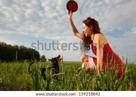 Young woman is playing with her dog with Frisbee - stock photo