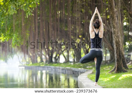 Young woman is practicing yoga at the park - stock photo