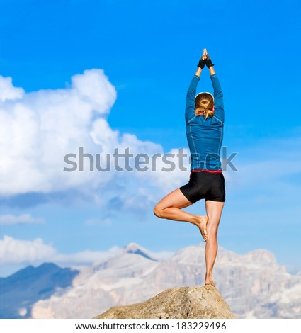 Young woman is practicing yoga in the mountains  - stock photo
