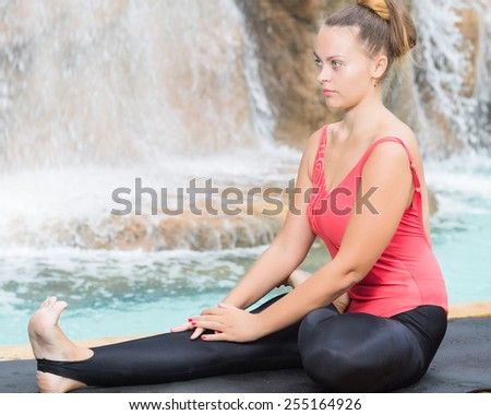 Young woman is practicing yoga near waterfall