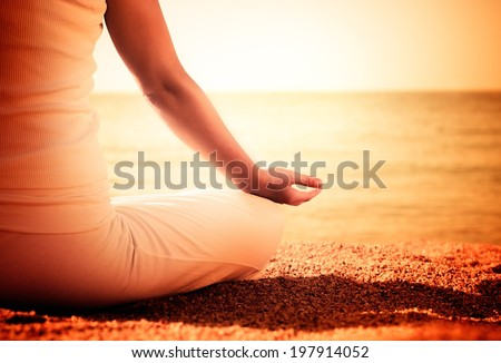 Young woman is practicing yoga on the beach. - stock photo