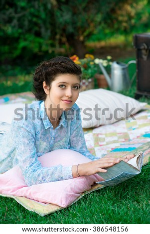 Young woman is reading a book in the city park.  Mindfulness, facial expression, emotions. Education and lifestyle. - stock photo