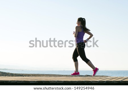 Young woman is running in sunny nature